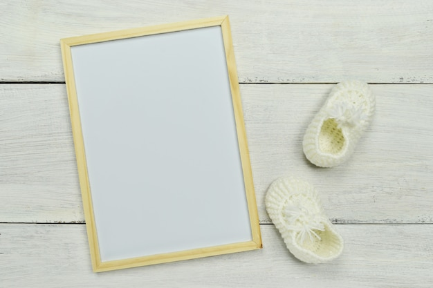 Bosquejo. marco vacío blanco con zapatitos y olla de árbol pequeño.