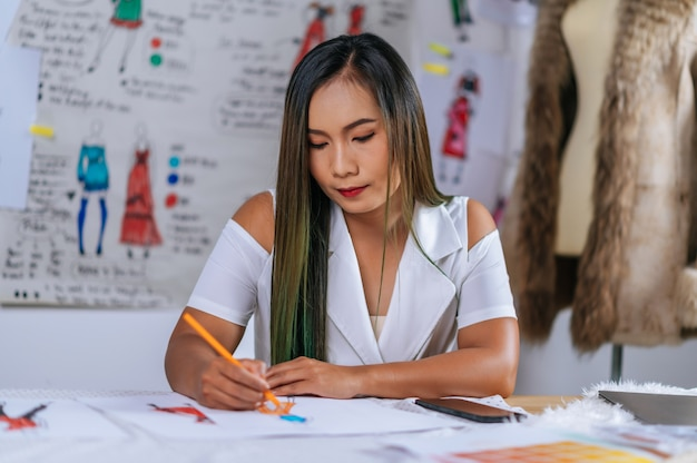 Bosquejo de la moda del dibujo femenino del diseñador asiático joven en la tienda del atelier moderno. hermoso abrigo en maniquí y ropa, imagen de boceto a bordo detrás de ella