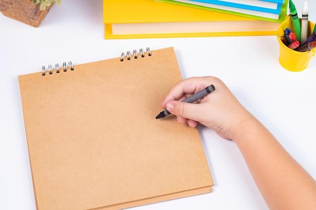 Bosquejo del muchacho de la visión superior algo en sketchbook en blanco en el fondo blanco / de nuevo a la escuela