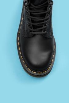 Bota negra sobre fondo azul. zapatos de moda bodegón. bota de combate clásica unisex negra con cordones. vista de cerca del maletero con espacio para copiar texto
