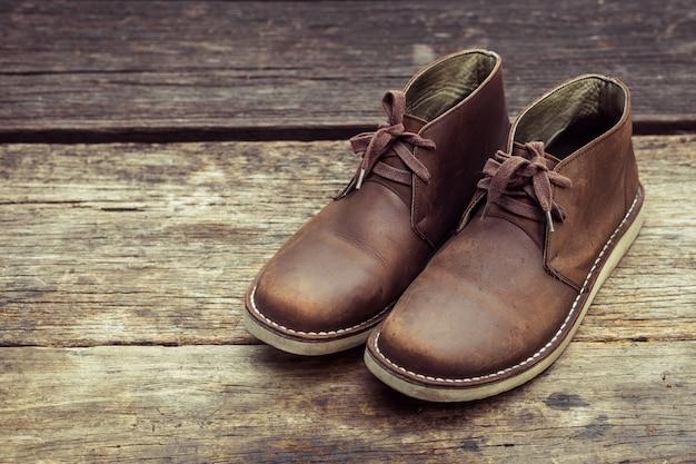 Botas con estilo marrón sobre fondo de madera, color retro