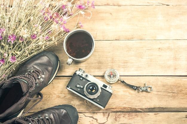 Botas, flores silvestres, una copa de metal, una brújula y otros atributos para una caminata en una superficie de madera. concepto de senderismo en las montañas o el bosque, turismo, tienda de campaña, campamento. vista plana, vista superior.