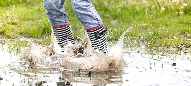 Botas de goma en un charco en el proceso de saltar con salpicaduras de agua de cerca.