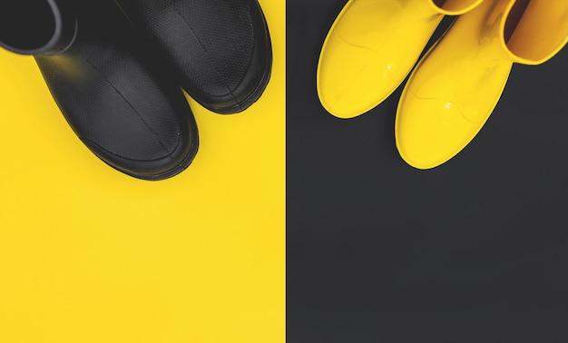 Botas de goma negras y amarillas sobre amarillo y negro.