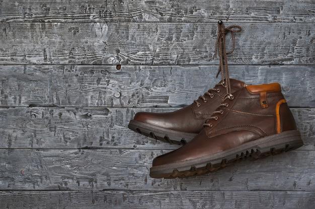 Botas de hombre con estilo marrón colgando de un clavo en la pared vintage.