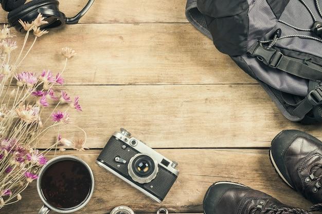 Botas, mochila, brújula y otros equipos de campamento sobre una superficie de madera. el concepto de senderismo en las montañas o el bosque, turismo, tienda de campaña, campamento. vista plana, vista superior.