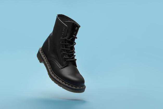 Botas negras en el aire sobre el fondo azul. zapatos de moda bodegón. bota de combate clásica unisex negra con cordones. vista de cerca de la bota de levitación con espacio para copiar texto
