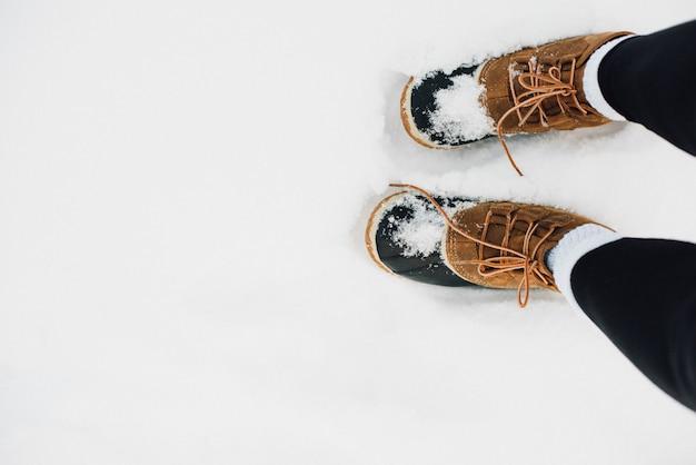 Botas de piel cálida cubiertas de nieve.