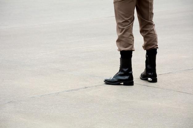 Botas de soldado de pie en el camino urbano.