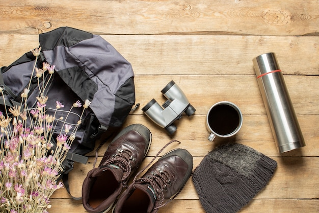 Botas para trail, mochila, binoculares, equipo de campamento sobre un fondo de madera. concepto de senderismo, turismo, campamento, montañas, bosque.