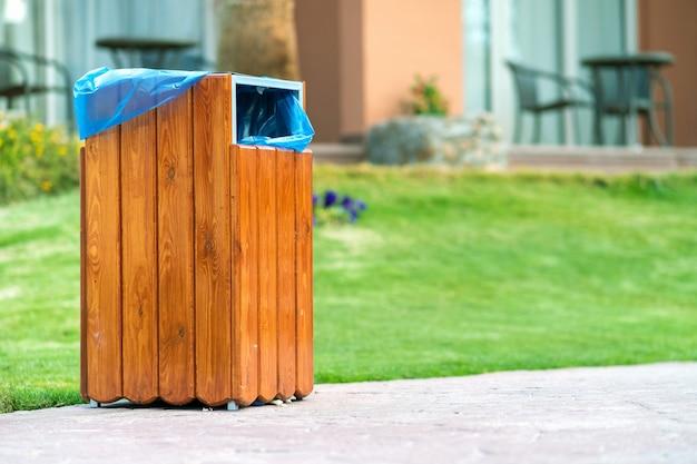 Bote de basura de madera amarillo al aire libre al lado de la acera en el parque.