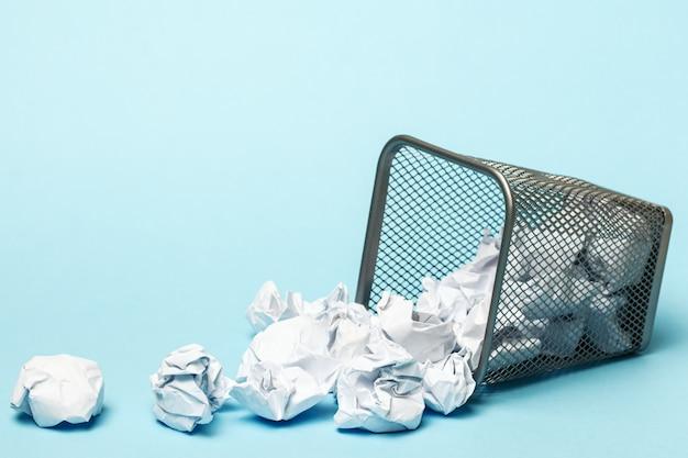 Bote de basura con papel arrugado sobre fondo azul.