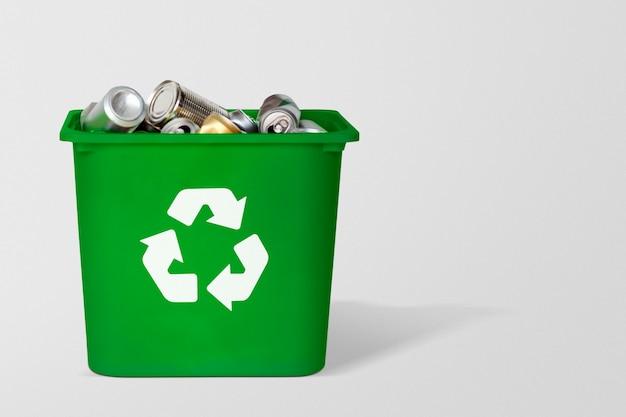 Bote de basura de reciclaje verde lleno de latas usadas con espacio de diseño sobre fondo gris