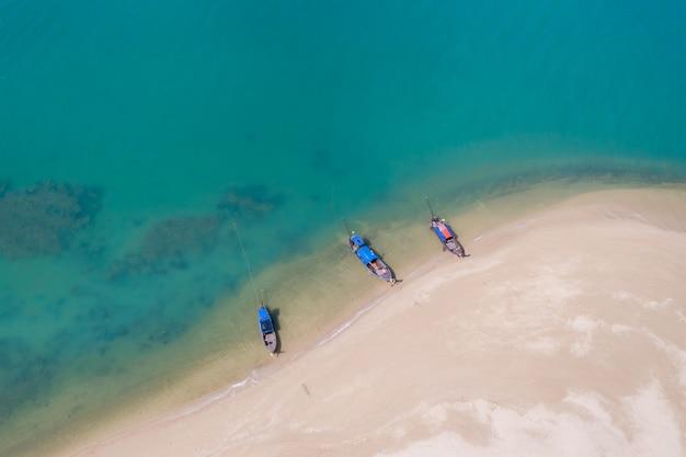 Bote de cola larga en la playa de arena