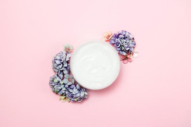 Un bote de crema con flores en rosa