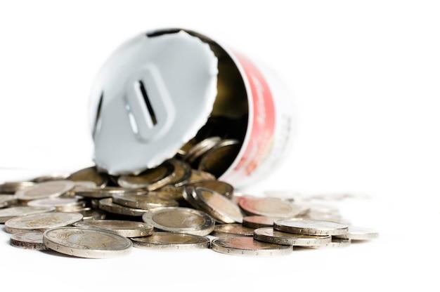 Bote de hojalata, abierto, con numerosas monedas de euro, caído a su alrededor. concepto de gastar el ahorro.