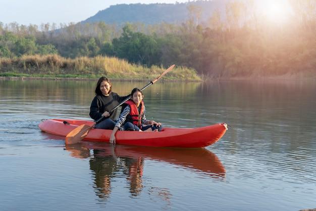 Bote de remo de madre e hija en aguas tranquilas.