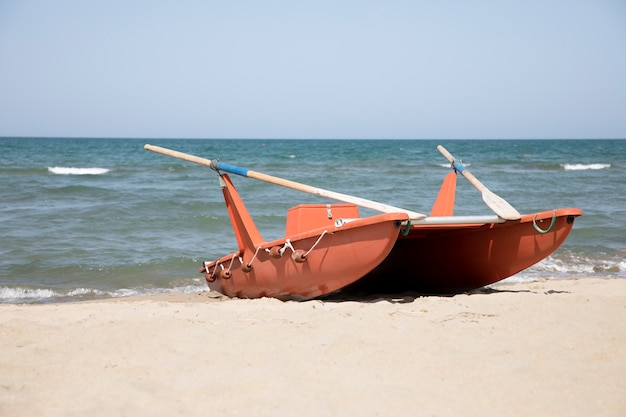 Bote de remo de tiro largo a la orilla del mar