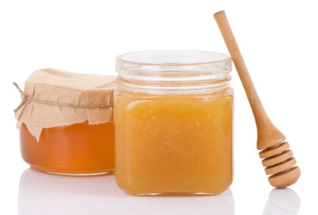 Bote de vidrio lleno de miel y palo aislado en blanco