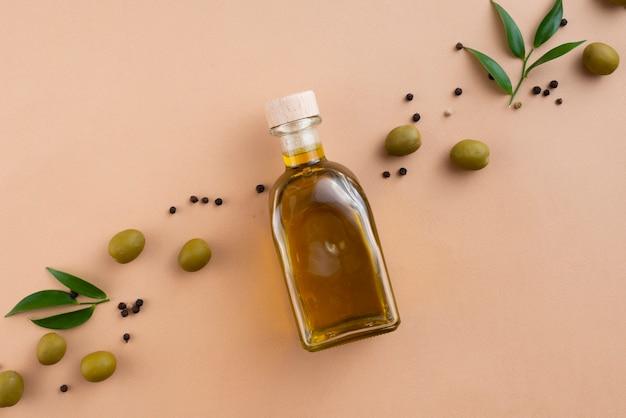 Botella de aceite de aceitunas con aceitunas y hojas a continuación