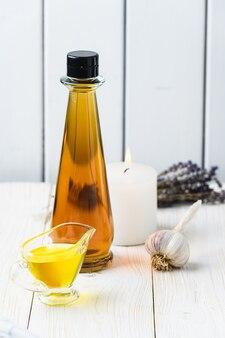Una botella de aceite, ajo y una vela sobre un fondo de madera blanca. estilo rústico.