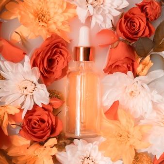 Botella de aceite de belleza en la leche con rosas coralinas y crisantemos