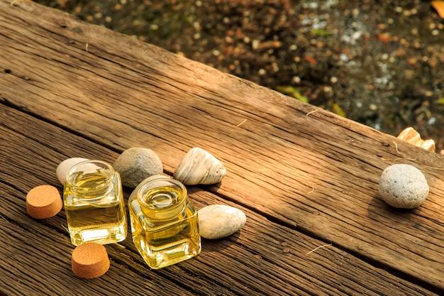 Botella de aceite esencial de aroma o spa con piedra zen en mesa de madera