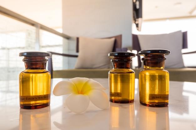 Botella de aceite esencial y flor de jazmín con la configuración de la flor del plumeria en la mesa de mármol.