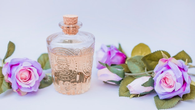 Botella de aceite esencial y flores falsas en superficie blanca