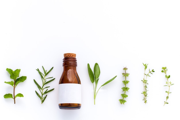 Botella de aceite esencial con hierbas sobre fondo blanco.