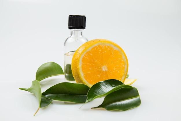 Botella de aceite esencial con hojas y rodaja de naranja de cerca