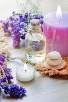 Botella con aceite esencial de lavanda, vela en mesa de madera.