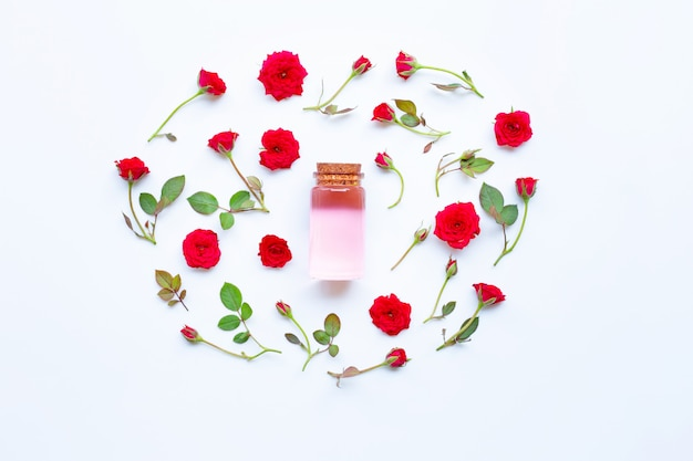 Botella de aceite esencial de rosa para aromaterapia en blanco.