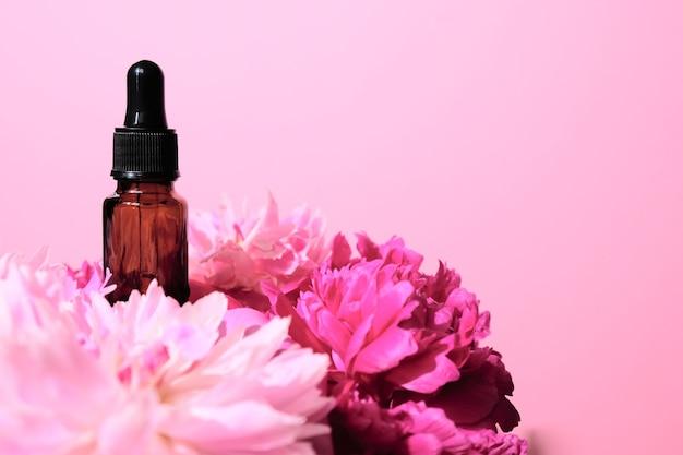 Botella de aceite esencial sobre un fondo rosa con flores rosas
