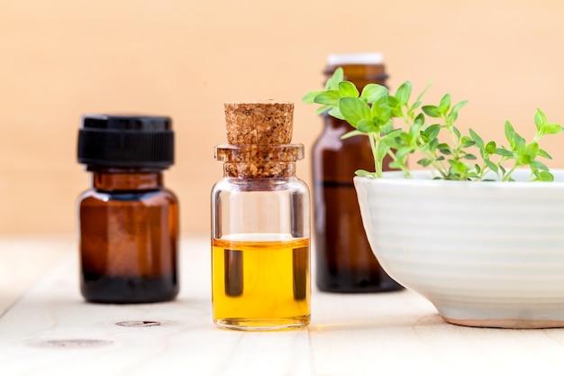 La botella de aceite esencial y el tomillo del limón hojean en fondo de madera.