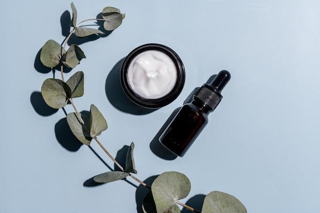 Botella de aceite esencial de vidrio ámbar marrón y tarro de crema facial con rama seca de eucalipto sobre fondo azul. vista plana endecha, superior. maquetas de envases de productos de belleza orgánicos naturales.