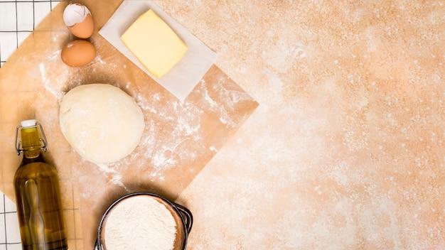Botella de aceite; harina; bloque de mantequilla huevos y bola de masa en el mostrador de la cocina.