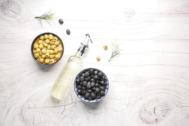 Botella de aceite de oliva aceituna verde y negra en un recipiente sobre la mesa de madera