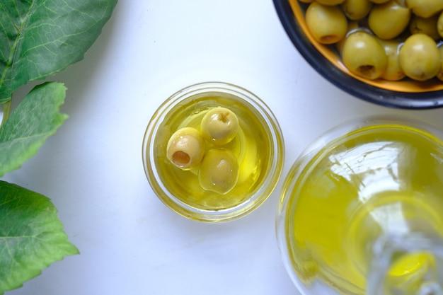 Botella de aceite de oliva y aceitunas frescas en un recipiente en blanco