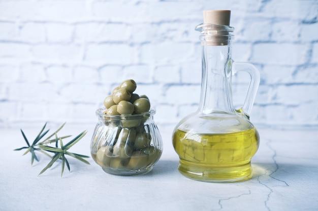 Botella de aceite de oliva y aceitunas frescas en un recipiente sobre la mesa de madera