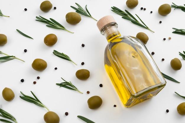 Botella de aceite de oliva con aceitunas y hojas alrededor