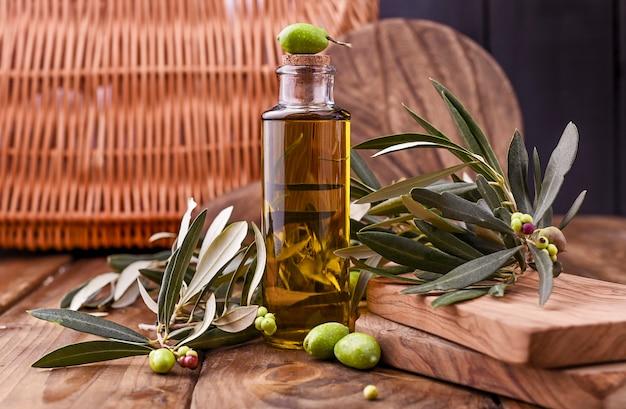 Botella de aceite de oliva con aceitunas y hojas.
