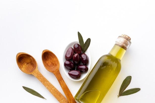 Botella de aceite de oliva aceitunas moradas y cucharas de madera