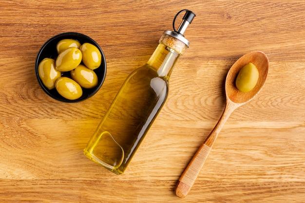 Botella de aceite de oliva cuchara de madera y aceitunas amarillas