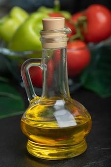 Botella de aceite de oliva frente a verduras frescas.