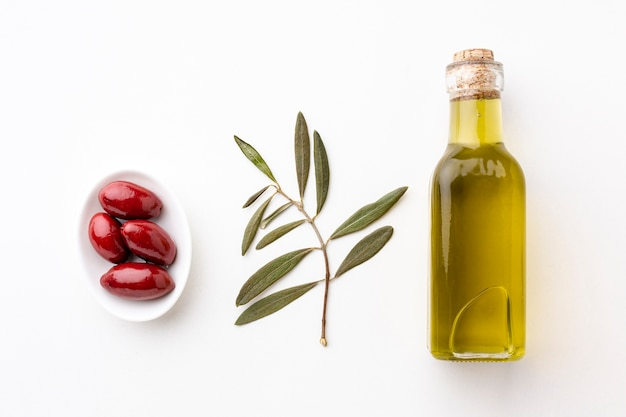 Botella de aceite de oliva con hojas y aceitunas rojas.