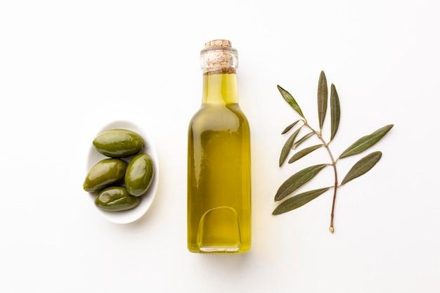 Botella de aceite de oliva con hojas y aceitunas verdes.