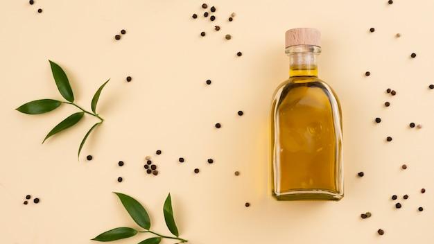Botella de aceite de oliva con hojas junto a la mesa