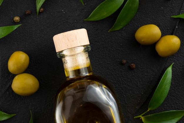 Botella de aceite de oliva con olves y hojas a continuación