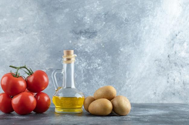Botella de aceite de oliva, patatas y tomates sobre fondo de mármol